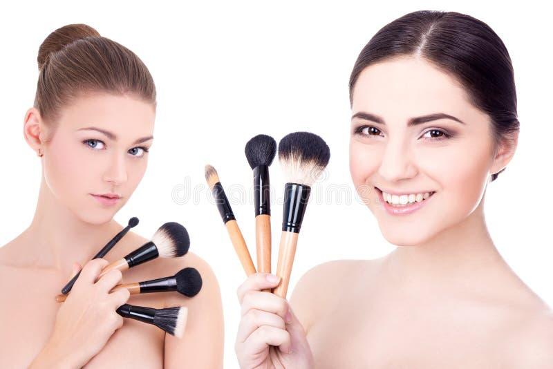 Duas mulheres bonitas novas com compõem as escovas isoladas no branco imagens de stock