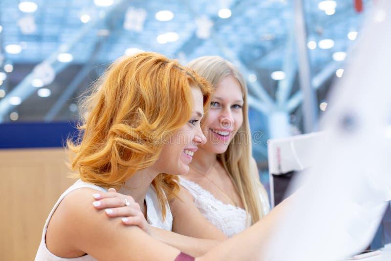 Duas mulheres bonitas novas em uma agência de viagens que escolhe uma viagem das férias, usando a tela interativa fotografia de stock