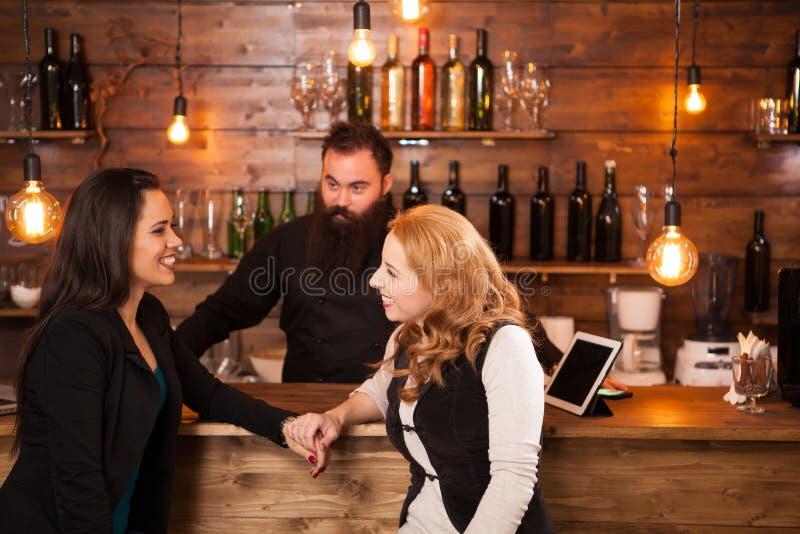 Duas mulheres bonitas novas que falam no bar imagem de stock royalty free