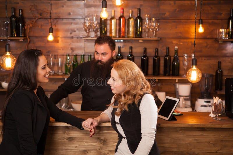 Duas mulheres bonitas novas que falam no bar fotos de stock royalty free