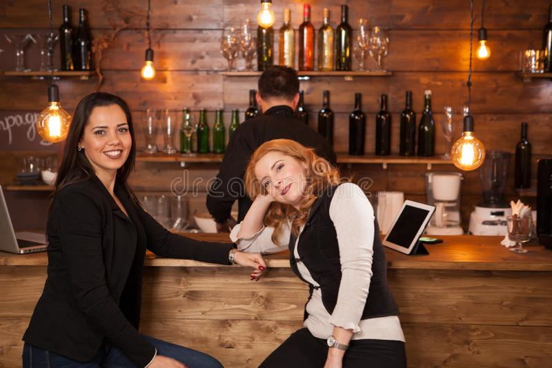 Duas mulheres bonitas novas que falam no bar imagem de stock