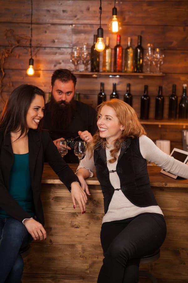Duas mulheres bonitas novas que falam no bar foto de stock