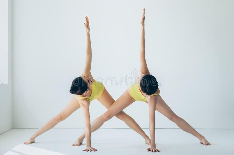 Duas mulheres bonitas novas que fazem o asana da ioga revolveram a posição do triângulo imagem de stock