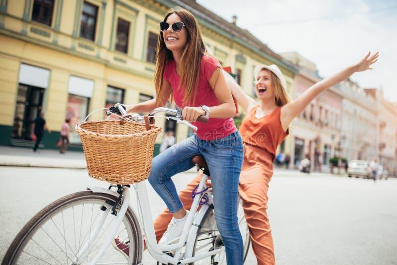 Duas mulheres bonitas que compram na bicicleta na cidade imagens de stock royalty free