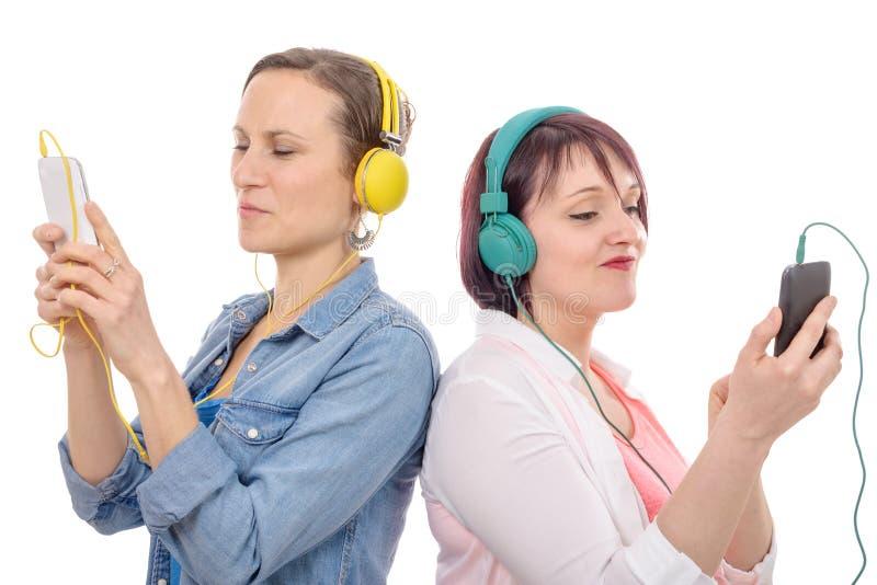 Duas mulheres bonitas que escutam a música com fones de ouvido fotografia de stock royalty free