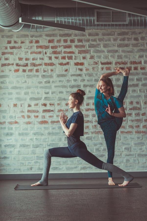 Duas mulheres bonitas que fazem a ioga do sócio no estúdio da ioga oposto à parede de tijolo foto de stock