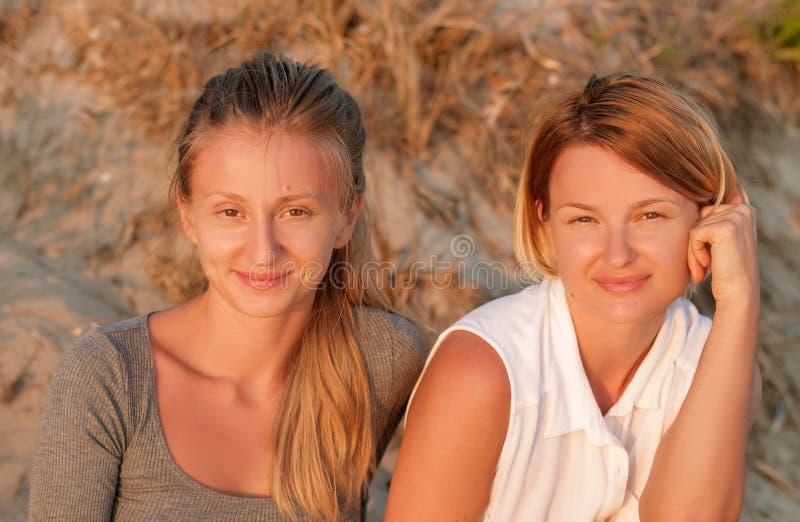 Duas mulheres bonitas que sentam-se na areia no olhar da praia no por do sol fotos de stock royalty free