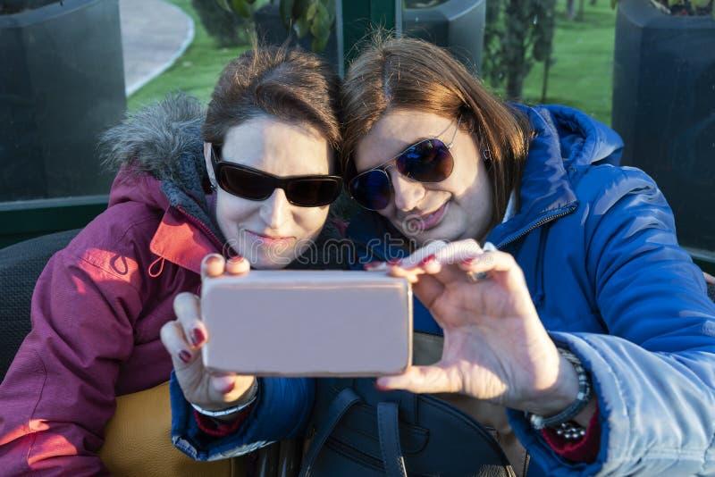 Duas mulheres bonitas que tomam um selfie com seu telefone celular imagens de stock