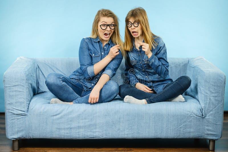 Duas mulheres chocadas que guardam monóculos falsificados na vara foto de stock