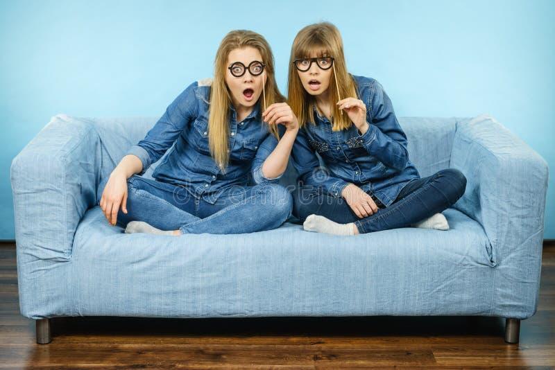 Duas mulheres chocadas que guardam monóculos falsificados na vara fotos de stock royalty free