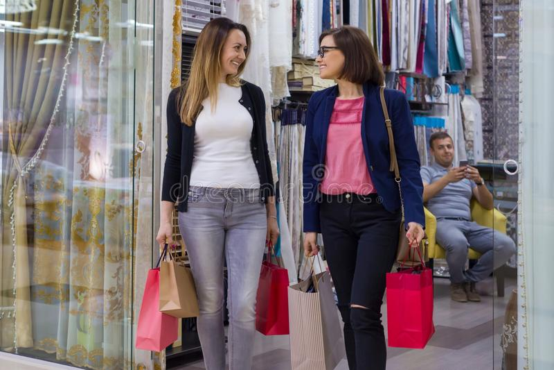 Duas mulheres com os sacos de compras na alameda Loja do fundo para a decoração home e telas interiores fotos de stock