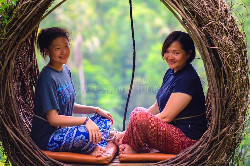 Duas mulheres consideravelmente asiáticas que sentam-se no ninho da palha, Ubud, Bali, 05 01 2019 Fim acima foto de stock
