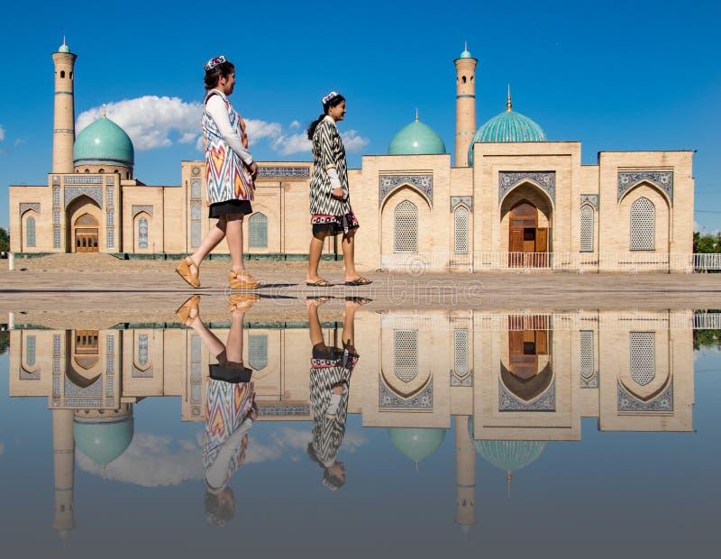 Duas mulheres dão uma volta na frente da mesquita da Khast-imã, refletida dentro foto de stock
