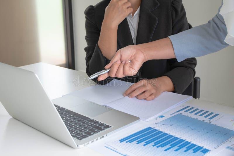 Duas mulheres de negócio analisaram a carta, ajustaram alvos para o sucesso novo da gestão imagem de stock