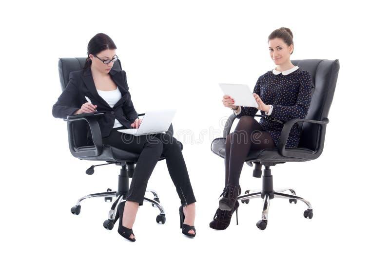 Duas mulheres de negócio bonitas que sentam-se em cadeiras do escritório com tabela fotos de stock