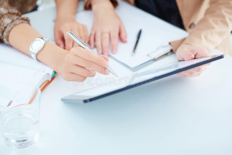 Duas mulheres de negócio em uma reunião que discutem a informação em um tabuleta-PC fotos de stock