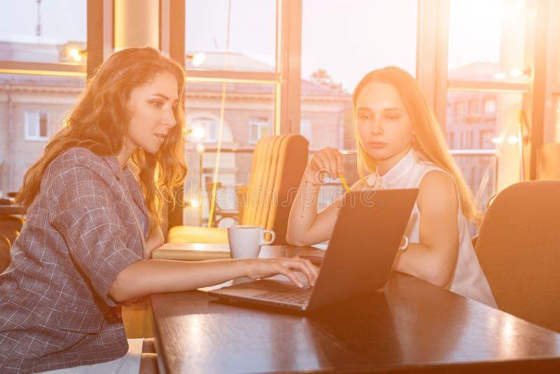 Duas mulheres de negócio estão sentando-se na tabela, trabalhando em um portátil, têm a conversação sobre novo começam acima no c foto de stock royalty free