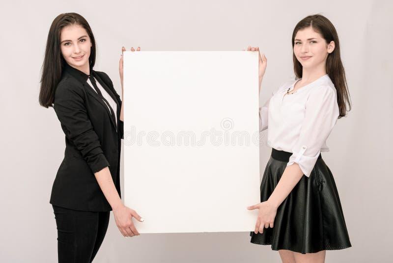 Duas mulheres de negócio novas de sorriso felizes que levam o signbo vazio grande fotos de stock
