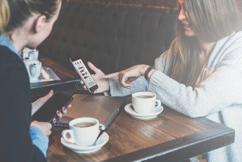 Duas mulheres de negócio novas que sentam-se na tabela e que usam smartphones Mulher que mostra gráficos do colega na tela do sma imagem de stock royalty free