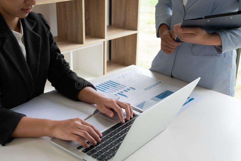 Duas mulheres de negócio que discutem as cartas e os gráficos que mostram os resultados imagem de stock royalty free