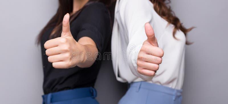 Duas mulheres de negócio que mostram os polegares acima do gesto imagens de stock