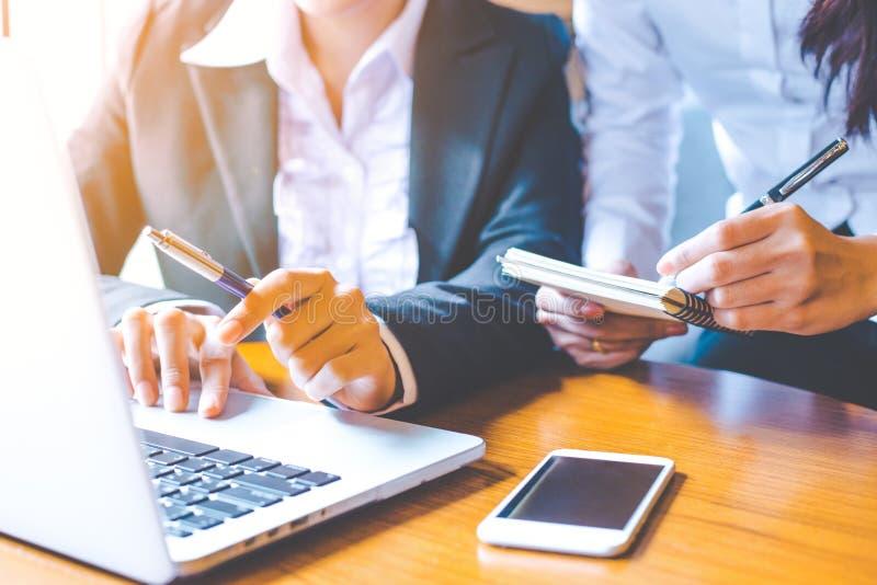 Duas mulheres de negócio que trabalham em um laptop e que escrevem sobre foto de stock royalty free