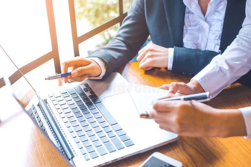 Duas mulheres de negócio que trabalham em um laptop e que escrevem sobre imagem de stock