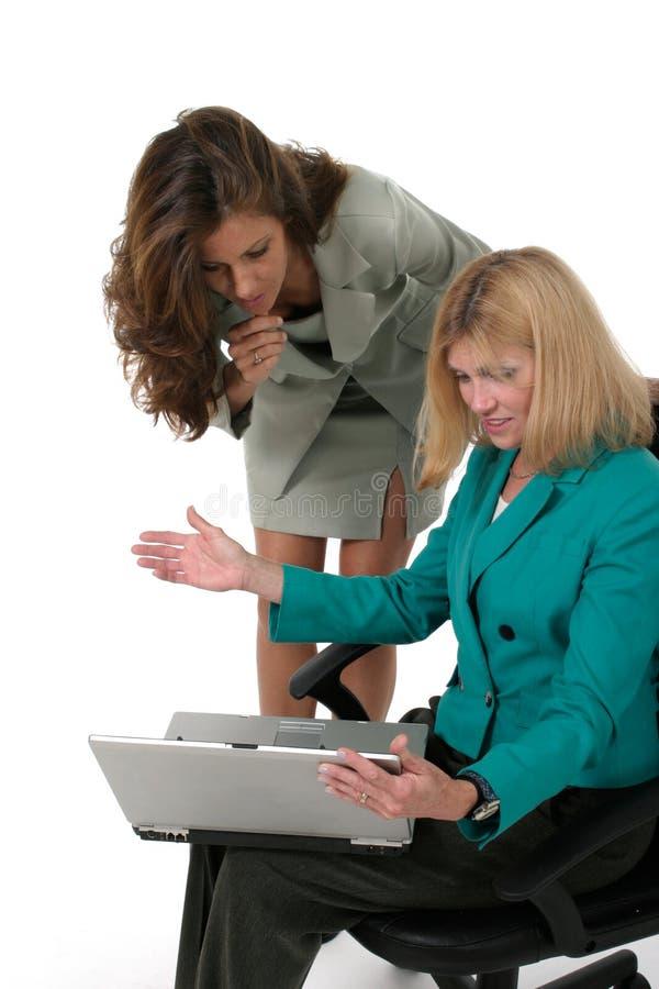 Duas mulheres de negócio que trabalham no portátil 12 foto de stock royalty free
