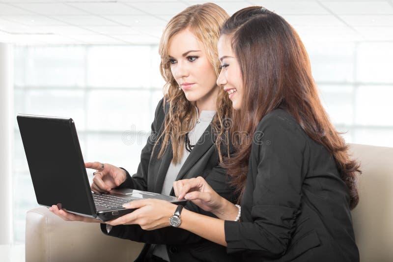 Duas mulheres de negócios amigáveis que sentam e que discutem ideias novas fotografia de stock royalty free