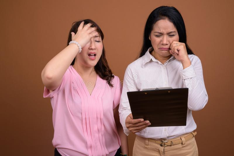 Duas mulheres de negócios asiáticas maduras junto contra o fundo marrom fotografia de stock royalty free