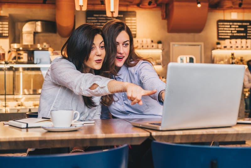 Duas mulheres de negócios novas As meninas com surpresa alegre mostram a mão no tela de computador, olhar das meninas no monitor  imagem de stock
