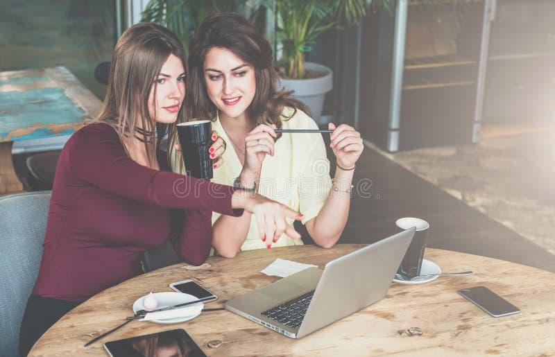 Duas mulheres de negócios novas estão sentando-se no café na tabela, trabalhando junto, menina estão apontando na tela do portáti fotos de stock