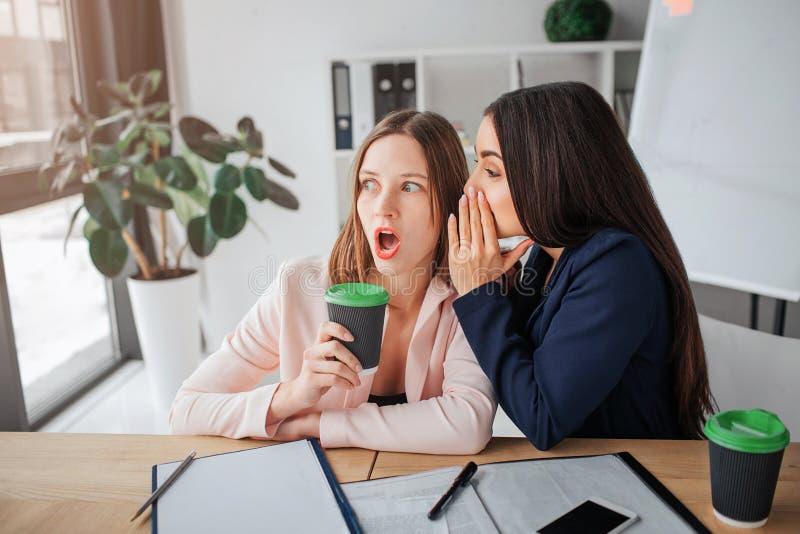 Duas mulheres de negócios novas sentam-se junto na sala na tabela Sussurro moreno à orelha uma outra pessoa fêmea Eles bisbolheti foto de stock