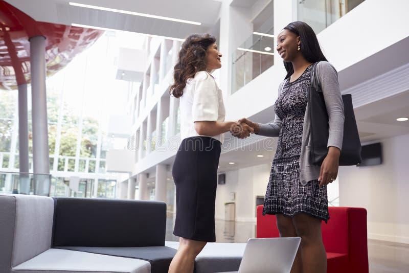 Duas mulheres de negócios que agitam as mãos na entrada do escritório moderno fotos de stock royalty free