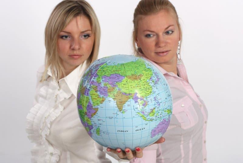 Duas mulheres de negócios que olham um globo imagens de stock royalty free