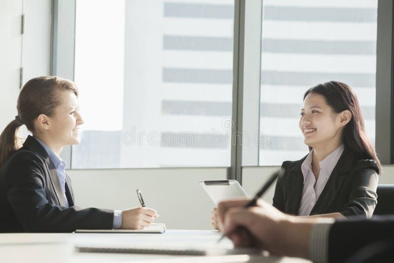 Duas mulheres de negócios que sorriem e que olham se durante uma reunião de negócios fotos de stock