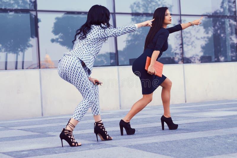 Duas mulheres de negócios vestiram-se na roupa formal à moda, têm o divertimento em uma baixa contra um arranha-céus foto de stock