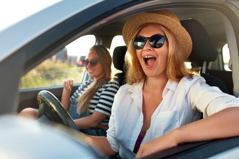 Duas mulheres de sorriso alegres novas em um carro na viagem das férias à praia do mar Menina nos vidros que conduzem um veículo  fotos de stock royalty free