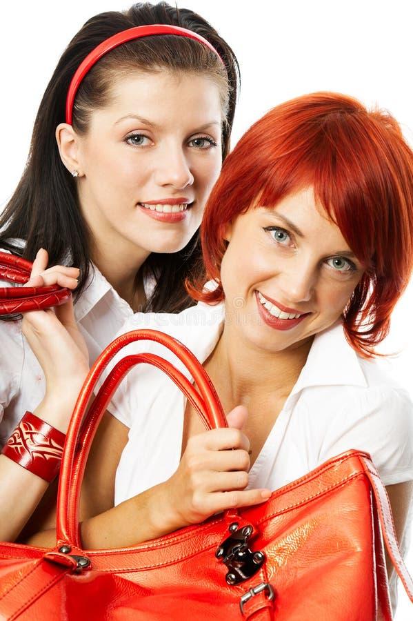 Duas mulheres de sorriso com bolsas vermelhas fotos de stock royalty free