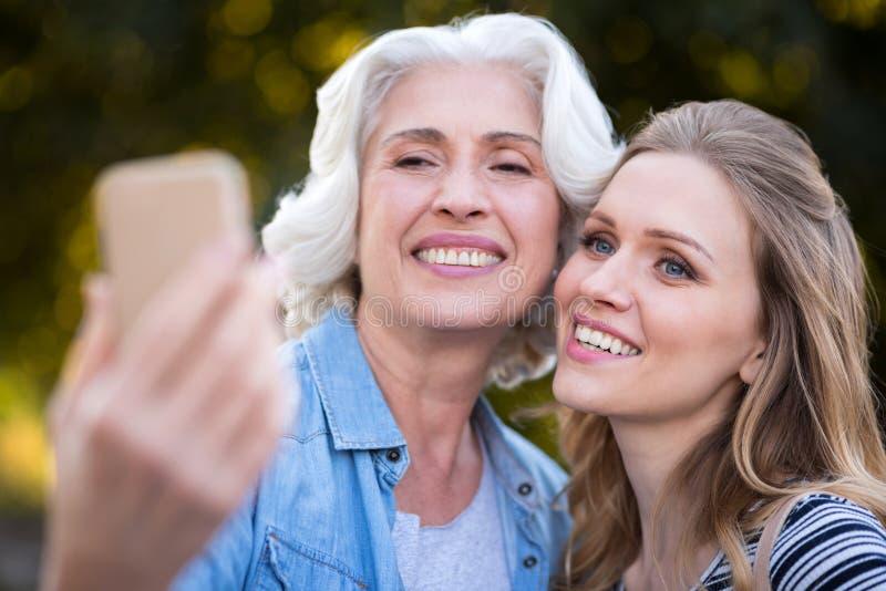Duas mulheres de sorriso de encantamento que tomam o selfie fotografia de stock royalty free
