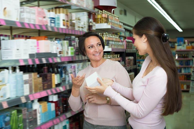 Duas mulheres de sorriso que escolhem o creme da prateleira fotografia de stock royalty free