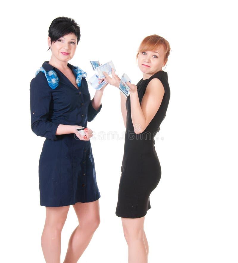 Duas mulheres de sorriso que guardaram o dinheiro imagens de stock royalty free