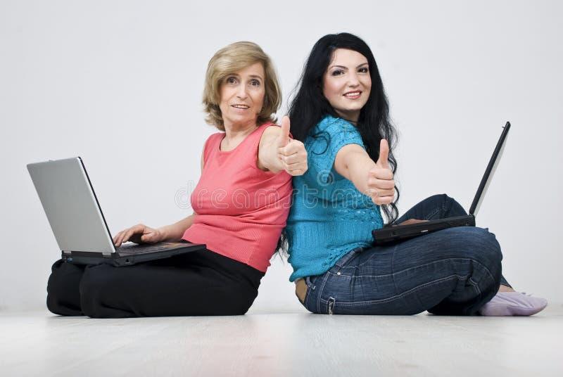 Duas mulheres de sorriso que sentam-se no assoalho com portáteis foto de stock royalty free