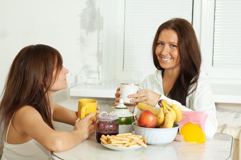 Duas mulheres de sorriso têm o chá fotografia de stock