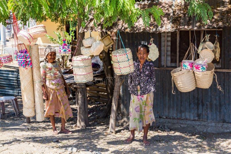 Duas mulheres de Timor oriental nativas idosas locais, rua que vende as cestas de vime tradicionais que penduram em cordas, perto fotos de stock