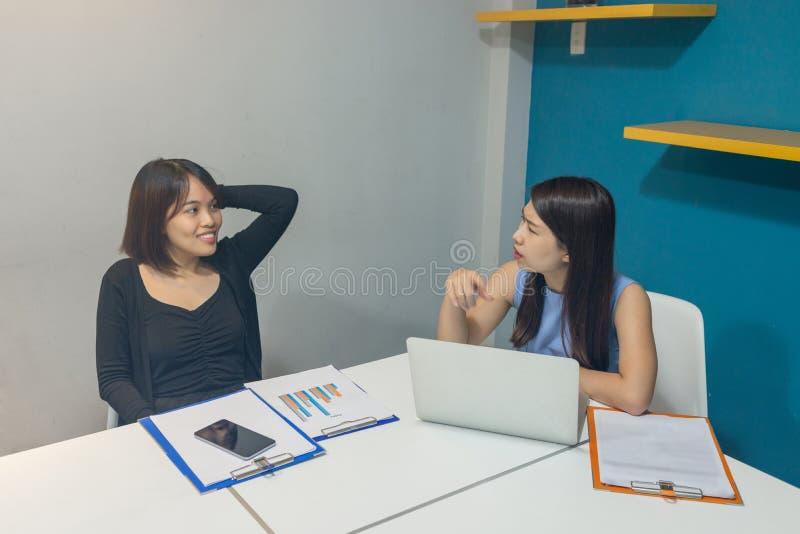 Duas mulheres do escritório compartilham de ideias e de opinião no escritório fotografia de stock royalty free