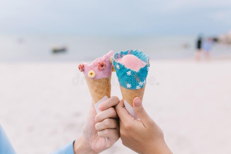 Duas mulheres do jovem adolescente das mãos que guardam o cone de gelado no verão na praia e no mar fotografia de stock royalty free