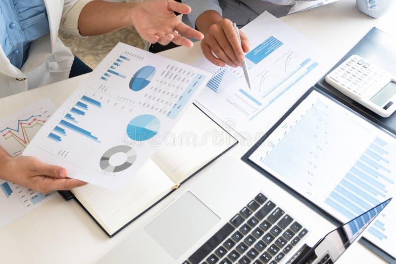 Duas mulheres do líder de negócio que discutem as cartas e os gráficos que mostram os resultados fotografia de stock