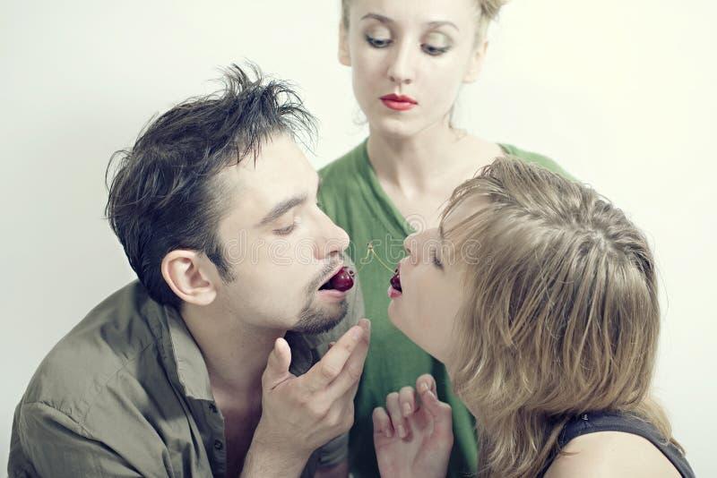 Duas mulheres e um homem com as cerejas maduras vermelhas foto de stock