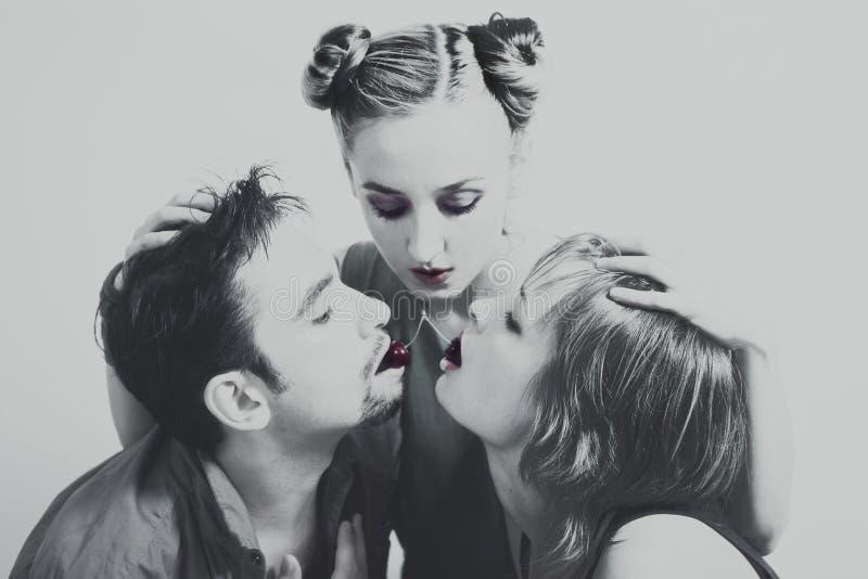 Duas mulheres e um homem com as cerejas maduras vermelhas imagem de stock